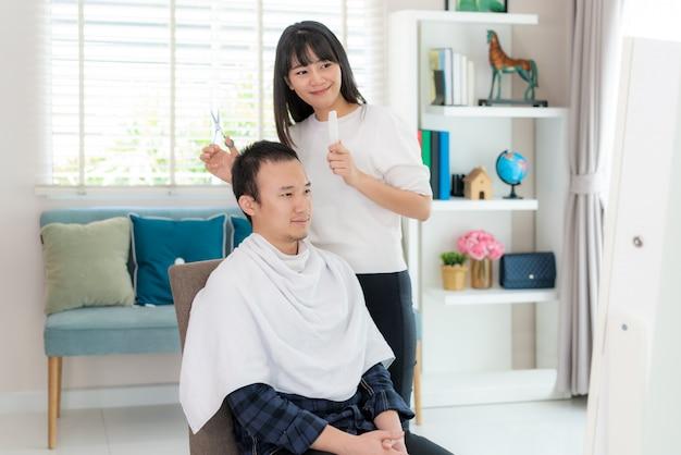 Azjatycki młody człowiek z dziewczyną fryzjerką przycinającą czarne włosy nożyczkami w domu, pozostają w domu w czasie izolacji domowej od nowego koronawirusa (2019-ncov) lub covid-19