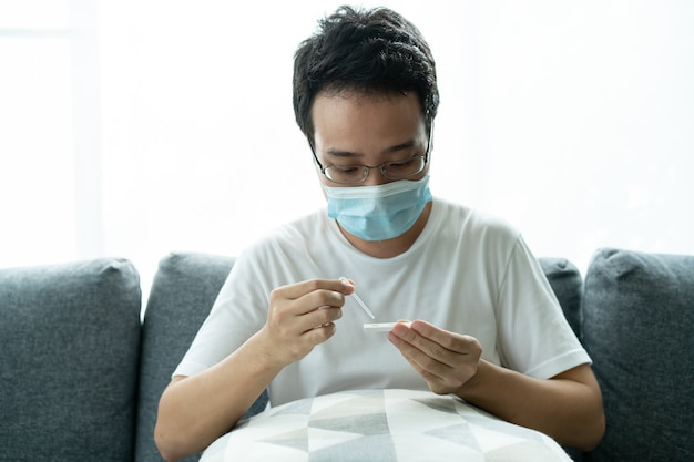 Azjatycki młody człowiek z higieniczną maską ochronną na twarz przy użyciu zestawu szybkiego testu sars 2019-ncov covid-19 na antygen koronawirusa - zestaw do testu ag w domu. szybki test na obecność antygenu covid-19.