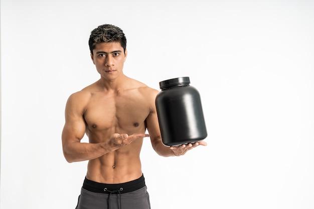 Azjatycki młody człowiek z umięśnionym ciałem nosi jedną ręką czarną butelkę, podczas gdy obecna stoi twarzą do przodu