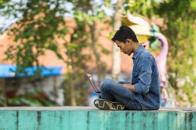 Azjatycki młody człowiek za pomocą komputera na zewnątrz
