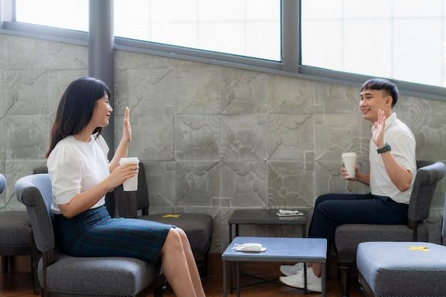 Azjatycki młody mężczyzna i kobieta siedzą po jednej osobie na jednym stole i pozdrawiają się i przywitają się z odległości 6 stóp, chronią przed wirusami covid-19 w przypadku dystansu społecznego z powodu ryzyka infekcji