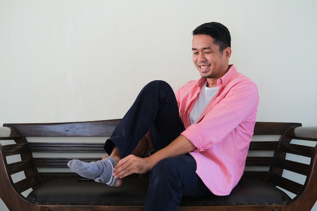 Azjatycki młody mężczyzna siedzi na drewnianej kanapie podczas noszenia skarpety