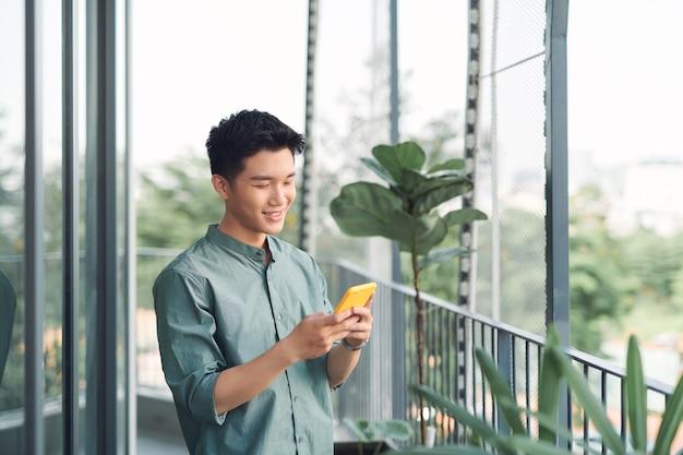 Azjatycki młody mężczyzna używający smartfona na balkonie
