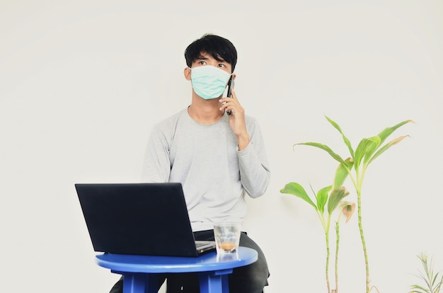 Azjatycki młody mężczyzna w masce siedzący przed laptopem zajęty swoją pracą