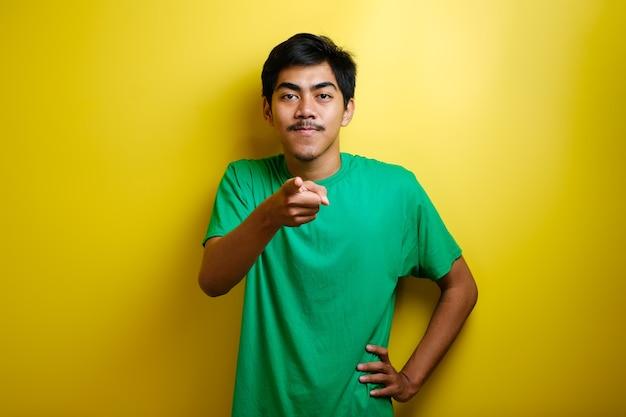 Azjatycki młody mężczyzna w zielonej koszulce skierowanej do przodu, patrząc na kamerę, wybierz gest na żółtym tle