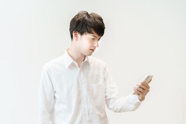 Azjatycki młody mężczyzna wpatrujący się w smartfona w oszołomieniu