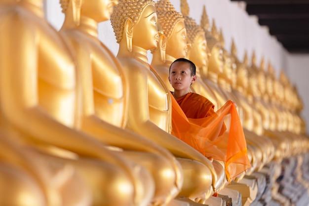 Azjatycki młody mnich-nowicjusz zakrywa posąg buddy w świątyni wat phutthai sawan w ayutthaya w tajlandii