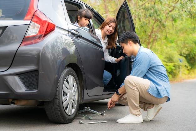 Azjatycki młody ojciec zmienia zmianę przebitej opony w swoim samochodzie, odkręcając nakrętki za pomocą klucza do kół, zanim podjeżdża do pojazdu, a matka i córka czekają