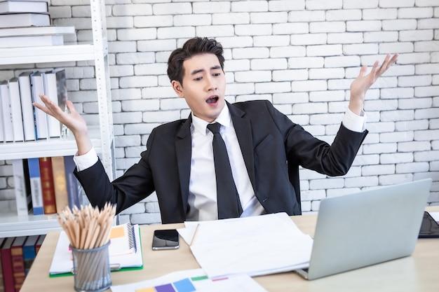 Azjatycki młody przystojny biznesmen zdziwił się, widząc laptopa i dokument biznesplan na drewnianym stole po stratach biznesowych i nie mogąc zaspokoić potrzeb klienta w tle pokoju biurowego