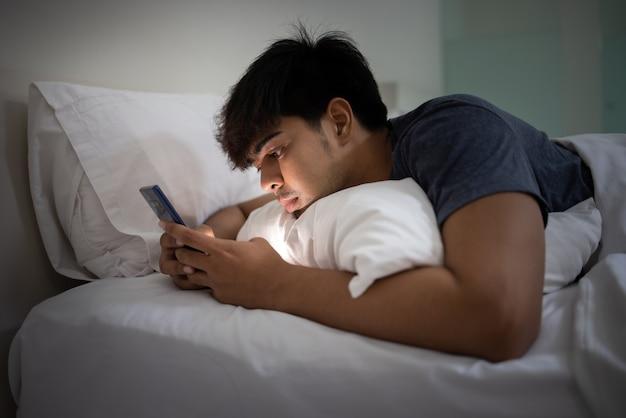 Azjatycki młody przystojny mężczyzna za pomocą smartfona na łóżku