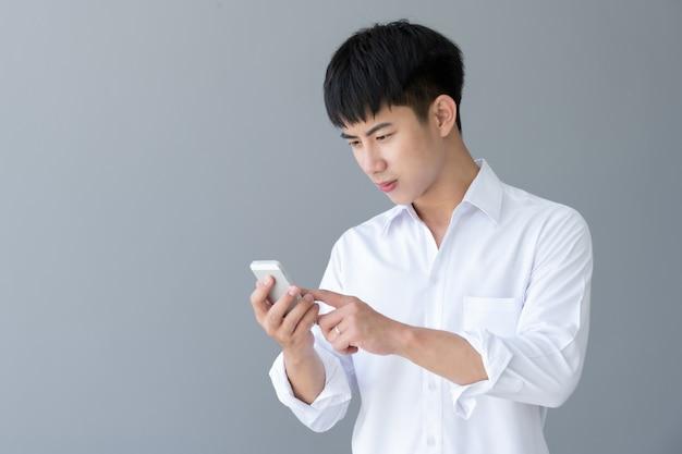 Azjatycki młody przystojny mężczyzna za pomocą smartfona