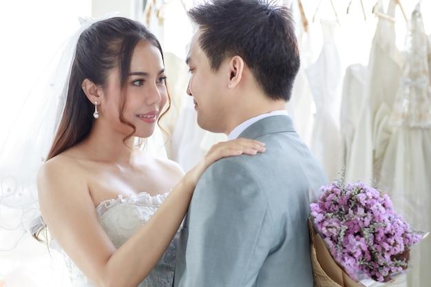 Azjatycki młody przystojny pan młody w szarym garniturze formalnym z krawatem stojący z piękną narzeczoną szczęśliwą w białej sukni ślubnej długiej, trzymając się za ręce i bukiet kwiatów razem w szatni.