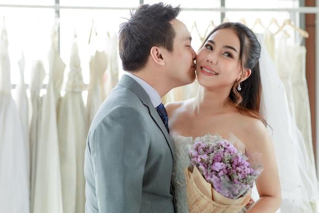 Azjatycki młody przystojny pan młody w szarym garniturze z krawatem stojący z piękną narzeczoną szczęśliwą w białej sukni ślubnej długiej, trzymając się za ręce i bukiet kwiatów razem w szatni i pocałunek w policzek.