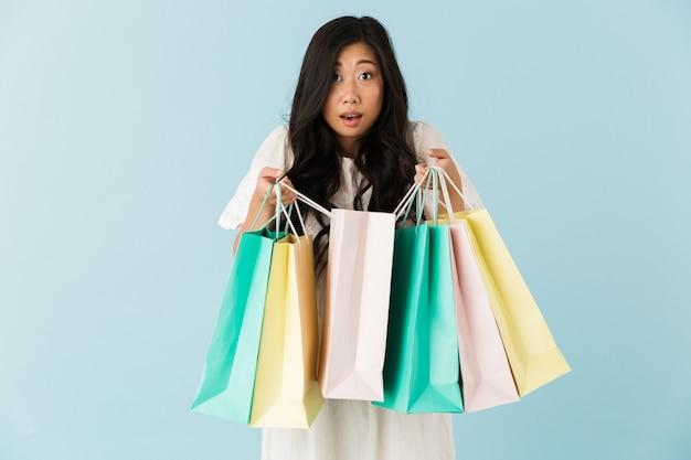 Azjatycki młody wstrząśnięty emocjonalny kobieta na białym tle nad niebieską ścianą trzymając torby na zakupy