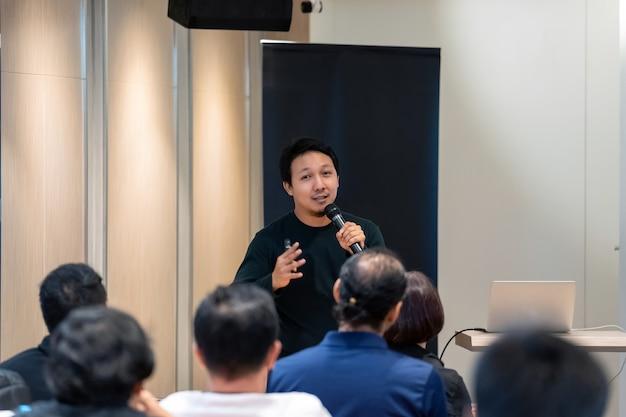 Azjatycki mówca z przypadkowym kostiumem na scenie przed pokojem z niskim światłem