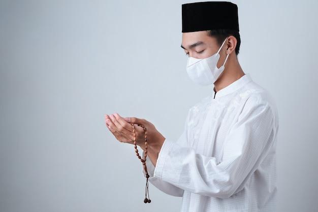 Azjatycki muzułmanin człowiek ubrany w muzułmańskie ubrania, trzymając koraliki modlitewne z maską medyczną