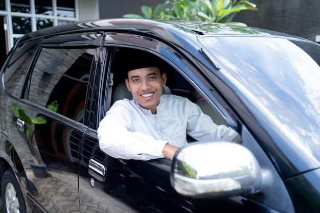 Azjatycki muzułmanin jadący samochodem z czapką