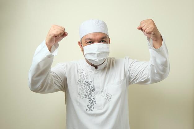Azjatycki muzułmanin noszący maskę tańczący radośnie radośnie świętujący dobre wieści