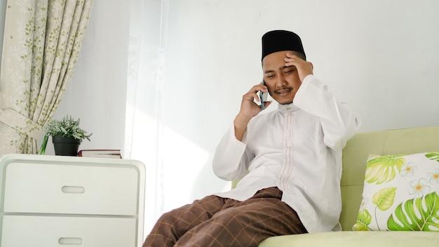 Azjatycki muzułmanin siedzi przy telefonie