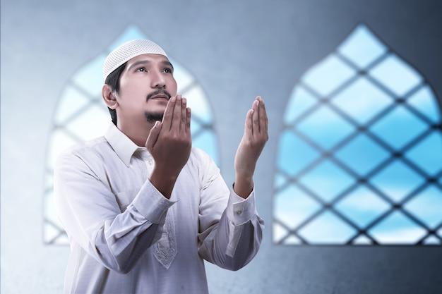 Azjatycki muzułmanin stojąc, podnosząc ręce i modląc się na meczecie
