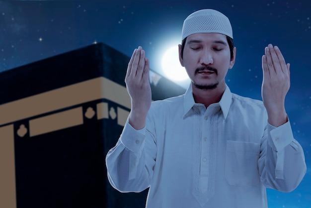 Azjatycki muzułmanin stojący i modlący się z widokiem kaaba i tłem sceny nocnej