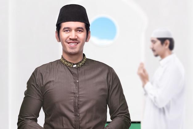 Azjatycki muzułmanin stojący z podniesionymi rękami i modlący się w meczecie