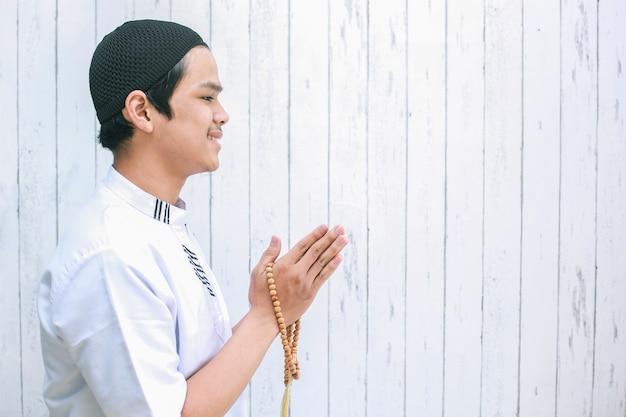 Azjatycki muzułmanin ubrany w koko trzymający koraliki modlitewne robi muzułmański uścisk dłoni na powitanie id al-fitr