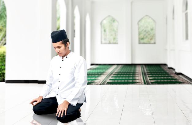 Azjatycki muzułmanin w pozycji modlącej się (salat) na meczecie