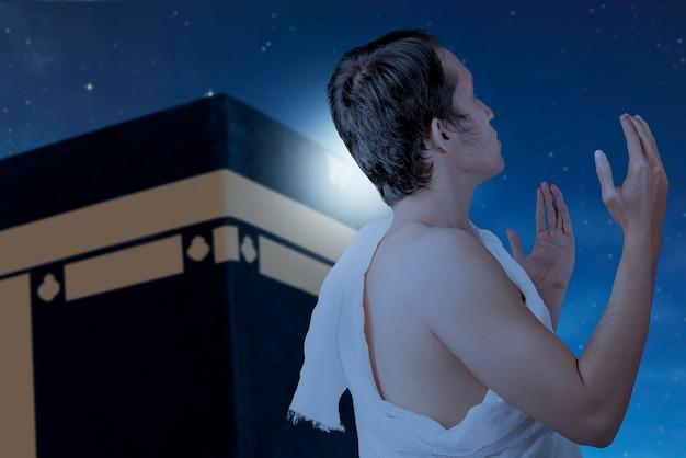 Azjatycki muzułmanin w ubraniach ihram stojący i modlący się z tłem kaaba i sceny nocnej