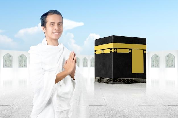 Azjatycki muzułmanin w ubraniach ihram stojący z gestem pozdrowienia z tłem kaaba