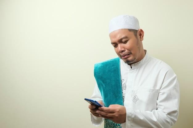 Azjatycki muzułmanin wygląda na smutnego, gdy odbiera wiadomości ze swojego smartfona