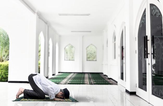 Azjatycki muzułmanin z dywanikiem w pozycji modlitewnej (salat)