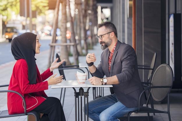 Azjatycki muzułmański bizneswoman w kawiarni rozmawia z klientem lub przyjacielem chłopca