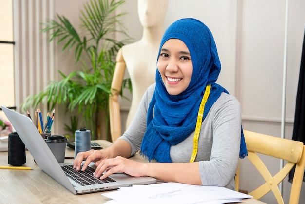 Azjatycki muzułmański kobieta projektant pracuje w jej krawieckim sklepie