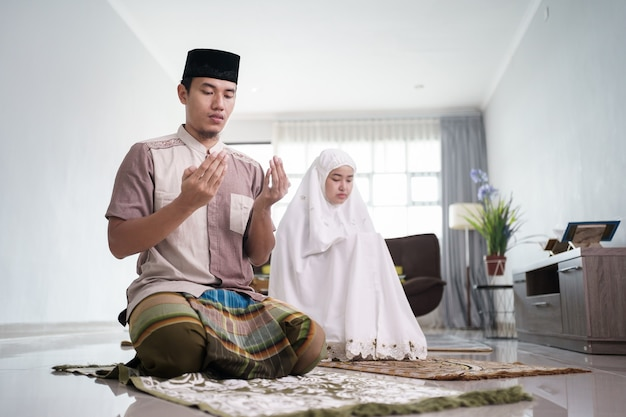 Azjatycki muzułmański mąż i żona modlą się razem w domu na dżamaah