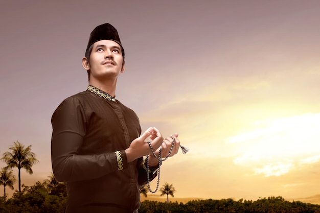 Azjatycki muzułmański mężczyzna modli się z modlitewnymi koralikami na jego rękach