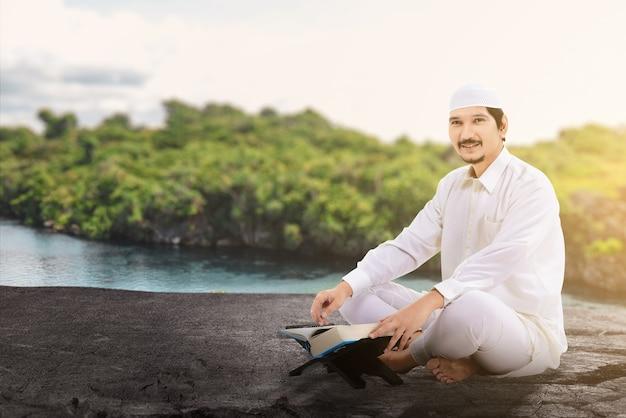 Azjatycki muzułmański mężczyzna siedzi i czyta koran na zewnątrz
