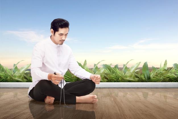Azjatycki muzułmański mężczyzna siedzi i ono modli się z modlitewnymi koralikami