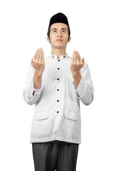 Azjatycki muzułmański mężczyzna stoi podczas gdy podnoszący rękę i ono modli się
