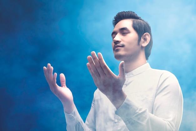 Azjatycki muzułmański mężczyzna stojący, trzymając ręce i modląc się na kolorowym tle