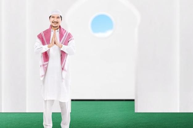 Azjatycki muzułmański mężczyzna stojący z pozdrowieniami na meczecie