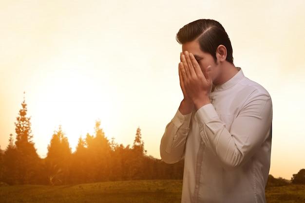 Azjatycki muzułmański mężczyzna z traditonal smokingowym modleniem