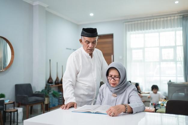 Azjatycki muzułmański starszy mężczyzna uczy żonę czytania koranu lub koranu w salonie. muzułmańska para modli się w domu