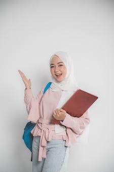 Azjatycki muzułmański student trzymając laptopa przed białym na białym tle pokazano