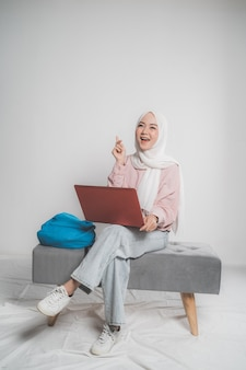 Azjatycki muzułmański uczeń trzyma laptopa przed białym tle na białym tle siedzi i myśli patrząc w górę