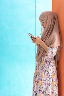 Azjatycki muzułmański uczeń używa telefonu komórkowego