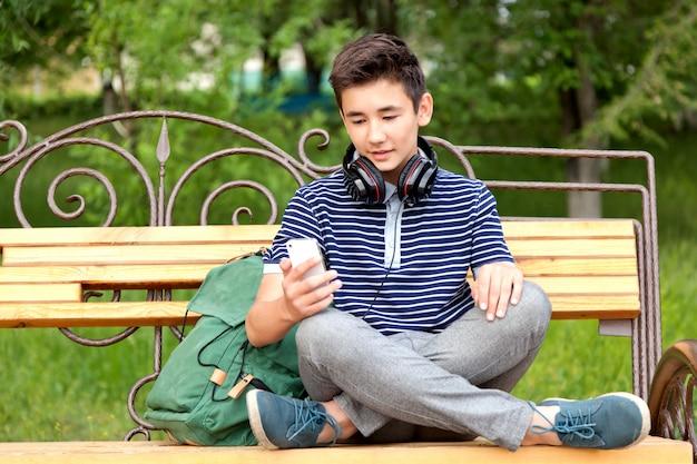 Azjatycki nastolatek siedzi na ławce z szkolnym plecakiem, telefonem komórkowym i słuchawkami. powrót do szkoły.
