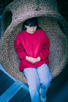 Azjatycki nastolatek siedzi w bambusowej huśtawce na tarasie domu
