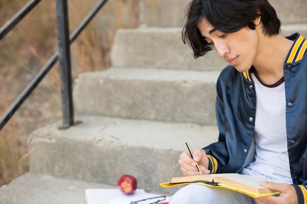 Azjatycki nastolatek siedzi z książką na schodach