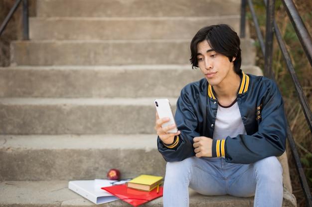 Azjatycki nastolatek siedzi z telefonem na schodach